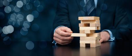Metafoor van de risico's in het bedrijfsleven. Risicomanagement concept. Zakenman verwijderen één stuk van de toren.
