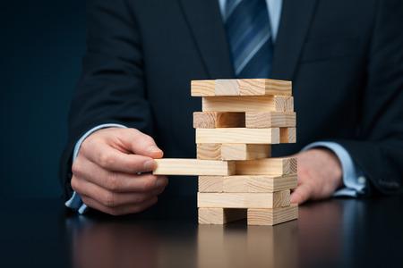 Métaphore du risque dans les affaires. concept de gestion des risques. Homme d'affaires supprimer une seule pièce de la tour. Composition de la bannière large avec bokeh en arrière-plan.