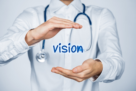 medical practitioner: Protect vision concept. Doctor (medical practitioner) with protective gesture and text vision. Stock Photo