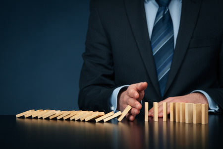 interruption: Businessman stop domino effect. Risk management concept, leadership has solution for problem.