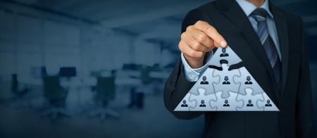 jerarquia: CEO, el liderazgo y el concepto de jerarquía corporativa - reclutador equipo completo representado por puzzle en el esquema de la pirámide por una persona líder (CEO). composición de la bandera de ancho, con oficinas en el fondo. Foto de archivo