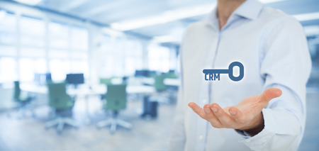 managerial: Key to successful CRM concept. Businessman offer Customer Relationship Management solution, represented by key with text CRM, office in background.