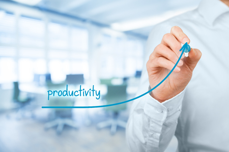 productividad: Aumentar la productividad concepto personal o de empresa. El hombre de negocios representado por el aumento en el aumento de la mano cartas en la productividad de la palabra. Oficina en segundo plano. Foto de archivo