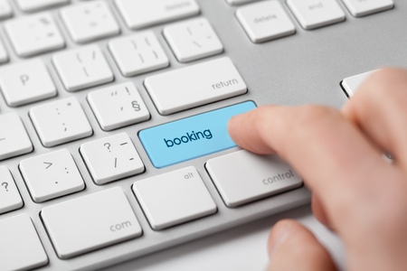 Online booking concept. Man click on booking button on keyboard.