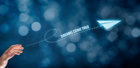 come up: Dreams come true concept. Hand throw a paper plane symbolizing dreams. Wide banner composition with bokeh background.