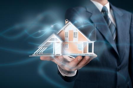 Makelaar bieden intelligente huis, smart home en domotica concept. Model van het huis en draadloze communicatie vertegenwoordigd door futuristische graphics.