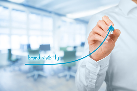 increase visibility: Brand visibility improvement concept. Brand manager (marketing specialist) draw growing graph with text brand visibility, office in background.