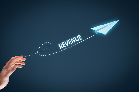 revenue: Increase revenue concept. Businessman throw a paper plane symbolizing growing revenue. Wide banner composition with bokeh in background.