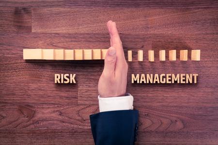 concepto de gestión de riesgos. gestor de riesgos (u otra persona de negocios) tiene la solución del problema. El hombre de negocios detiene efecto dominó, vista desde arriba.