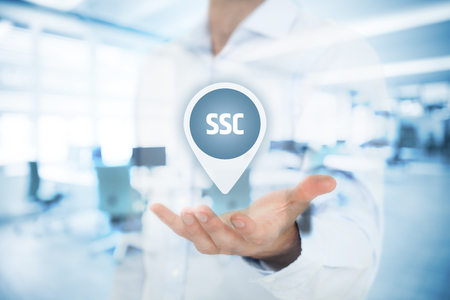 Shared services center (SSC) concept. Businessman hold virtual label with SSC acronym. Double exposed image with office in background.  Stock Photo