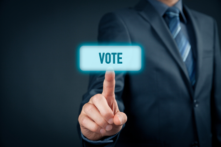 voting: Electronic (internet) voting concept (e-voting). Businessman click on virtual button with text vote.