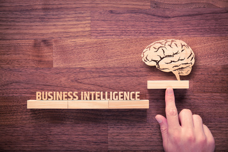 bi: Business intelligence (BI) concept. Businessman with icon of brain and text business intelligence.