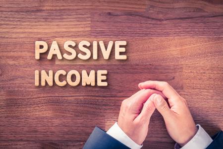 passive income: Passive income concept. Businessman hands in passive gesture and wooden text passive income. Stock Photo