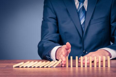 Risk manager stoppen domino-effect. Risicomanagement en verzekeringen concept, leiderschap heeft oplossing voor een probleem. Stockfoto