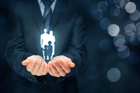 Family life insurance, family services and supporting families concepts. Businessman with protective gesture and silhouette representing young insured family. Left composition with bokeh in background.
