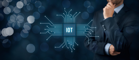 think about: Internet of things (IoT) concept. Businessman think about Internet of Things (IoT). Abstract chip connected with abstract devices represented by points. Stock Photo