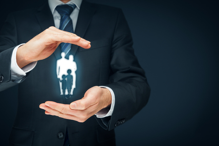 familias jovenes: Family life insurance, family services and supporting families concepts. Businessman with protective gesture and silhouette representing young insured family. Left composition.