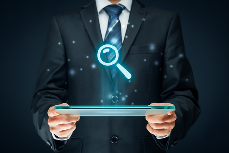 keywording: Search, find and SEO internet concepts. Businessman hold futuristic tablet with head-up display and symbol of loupe. Stock Photo