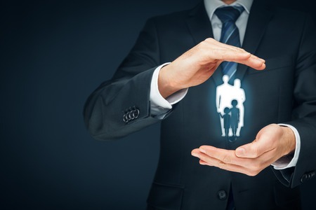 familias jovenes: Family life insurance, family services and supporting families concepts. Businessman with protective gesture and silhouette representing young insured family. Foto de archivo