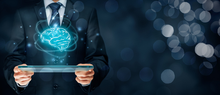 computer system: Artificial intelligence (AI), machine deep learning, data mining, expert system software, and another modern computer technologies concepts. Brain representing artificial intelligence and businessman holding futuristic tablet. Stock Photo