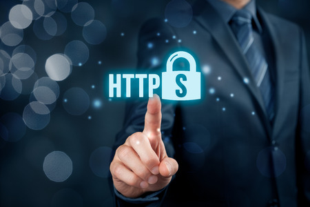 hypertext: HTTPS - secured internet concept. Businessman or programmer click on https text and padlock symbol. Stock Photo
