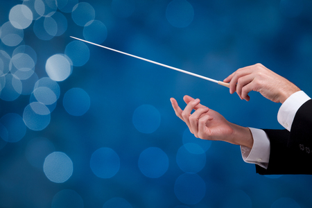 communication occupation: Male orchestra conductor hands with gesture, one with baton. Leadership and manager concepts.