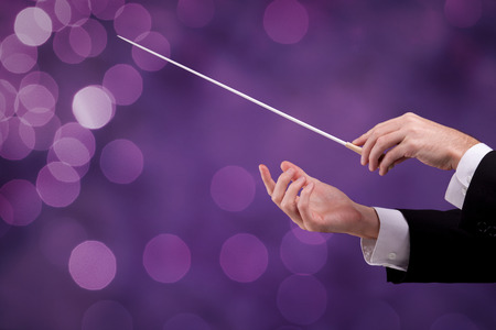 musica clasica: Male orchestra conductor hands with gesture, one with baton. Leadership and manager concepts.