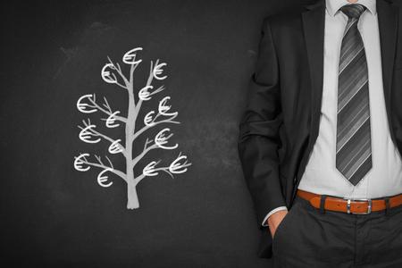 Homme d'affaires avec les mains dans le geste passif et l'arbre avec des dollars (concept de revenu passif).