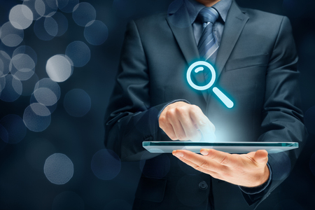 Search, find and SEO internet concepts. Businessman hold futuristic tablet with head-up display and symbol of loupe. Banque d'images