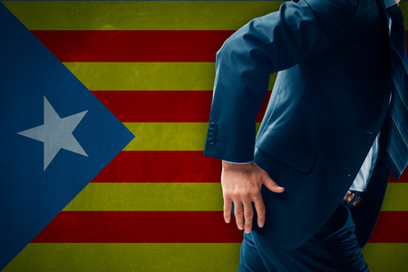 Catalonia separatism concept. Businessman (financier, bank employee, CEO, manager) run away (escape) from Catalonia represented by flag. Banque d'images