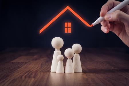 Concept d'assurance vie et propriété familiale. Figurines en bois représentant la famille et la maison de dessin à la main, symbole d'assurance. Banque d'images