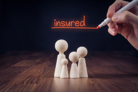 Family life insurance concept. Wooden figurines representing family and hand writing text insured. Banque d'images