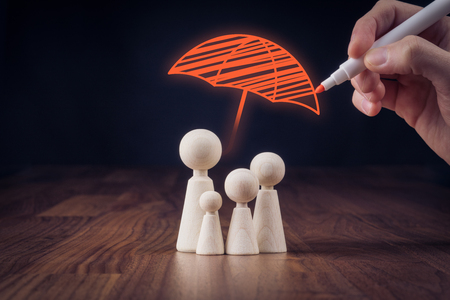 Family life and property insurance concept. Wooden figurines representing family and hand drawing umbrella, symbol of insurance. Banque d'images