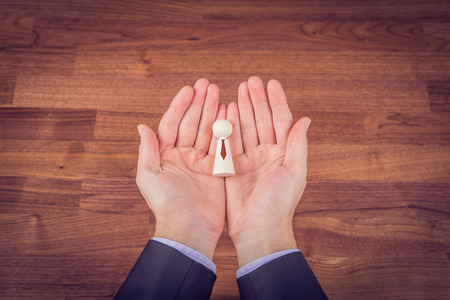 Human resources officer with new managerial employee or leadership represented by figurine.