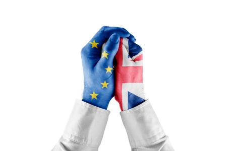 L'Union européenne restreint le concept de croissance de la Grande-Bretagne. Mains avec des drapeaux UE et GB et un geste restrictif (cravate, botte, brassard). Banque d'images