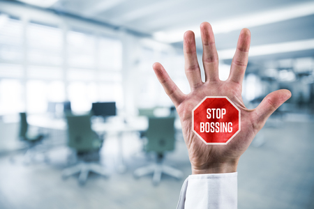 Stop bossing concept. Businessman or human resources officer with open hand with stop street sign and text Stop Bossing.