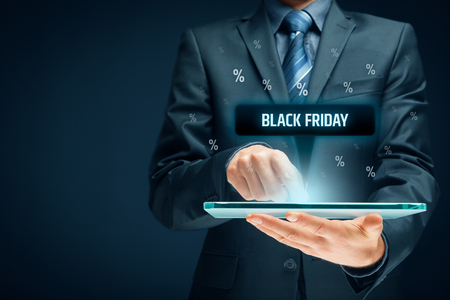 Black Friday sale concept. Businessman click on tablet on black Friday button, percentages on background.