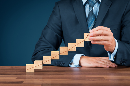 Businessman with wooden cubes with increasing graph.