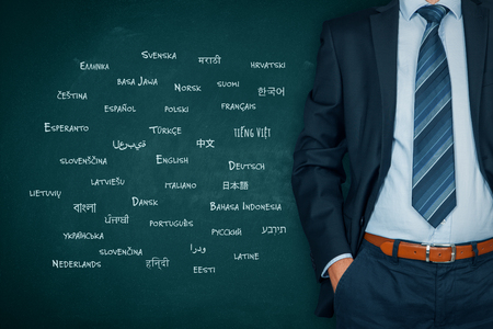 Translator professional, language course and multilingual person concept. Person with globally important languages written on school chalkboard.