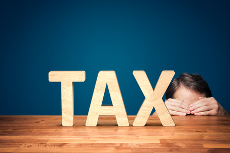 Accountant has a fear of the big tax. Worried or timid businessman is hiding behind the table against big taxes. Stock Photo