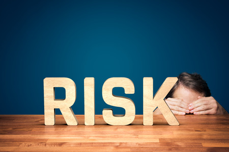 Risk manager has a fear of the risk in business. Worried or timid businessman is hiding behind the table against risk in business.