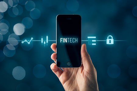 Fintech (financial technology) on smart phone concept. Hand with smart phone and text fintech and financial icons.