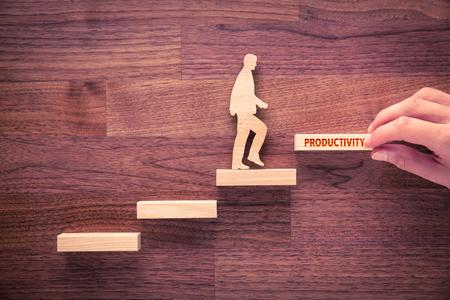 Coach motivieren zur Produktivitätssteigerung. Hand mit dem letzten Stück Treppe und Mensch aus Holz und Holztreppen, das letzte mit Textproduktivität. Standard-Bild