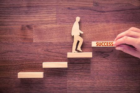 Trener motywuje do sukcesu. Ręka z ostatnim pokojem schodów i osoby wykonane z drewna i schodów drewnianych, ostatnie z tekstem sukcesu.