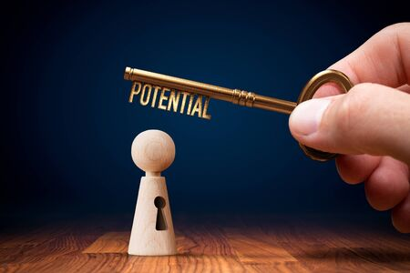 Coach has a key to unlock potential - motivation concept. Coach (manager, mentor, HR specialist) unlock leader potential and talent represented by wooden figurine and hand with key.