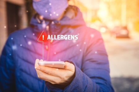 Increased concentration of allergens and polls in the air. Woman with mask and smart phone with notification or report about allergens. Modern healthcare concept.