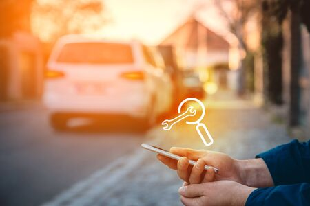 Search car service on smart phone. Smart car and new technologies in cars concept. Person with smart phone in hand sitting on the sidewalk and searching the nearest service.