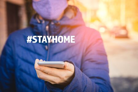 Stay home hashtag quarantine motivation concept. Quarantine (isolation) reduce contact with potentially infected person in times of epidemic. Woman with smart phone.