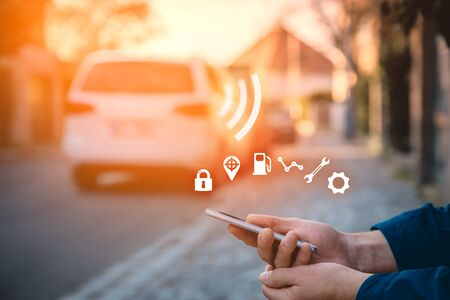 Intelligent car app on smart phone concept, intelligent vehicle and smart cars concept. Person with smart phone on street, car in background and wireless communication with car.