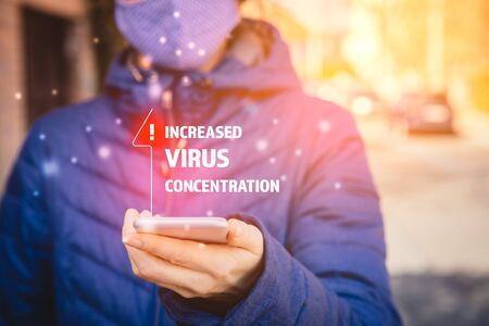 Increased virus concentration alert on smartphone concept. Woman with mask and smartphone with notification about virus in epidemic times.